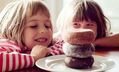 dos ninas mirando a los donuts con una sonrisa en la boca