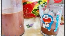 una vaso y botella de cristal con bebida de avena y chocolate