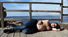 embarazada tumbada junto al mar