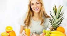 chica sonriente junto a frutas y zumos
